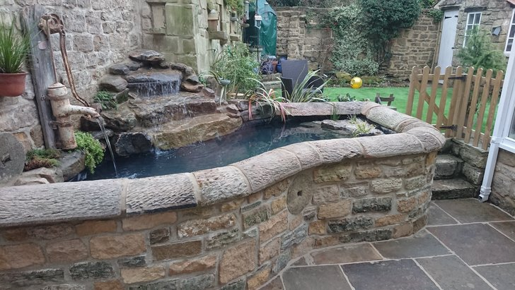 Bespoke stone water feature and pond including newly laid patio